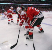 Duncan Keith of the Chicago Blackhawks battles for the puck with Daniel Cleary of the Detroit Red Wings in Game Seven of the Western Conference...