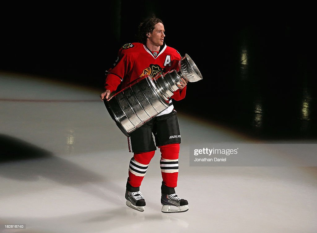 Duncan Keith #2 of the Chicago Blackhawks carries the Stanley Cup one last time during a ceremony before taking on the Washington Capitals at the United Center on October 1, 2013 in Chicago, Illinois.