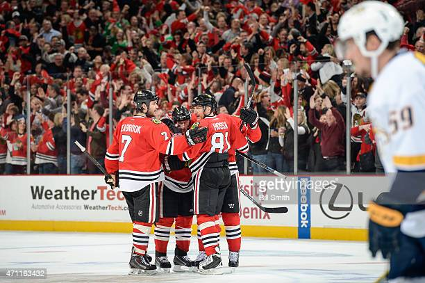 Duncan Keith of the Chicago Blackhawks celebrates with Brent Seabrook and Marian Hossa after scoring against the Nashville Predators in the third...