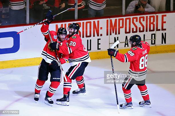 Duncan Keith of the Chicago Blackhawks celebrates with teammate Brandon Saad and Patrick Kane after scoring a goal in the second period against Ben...