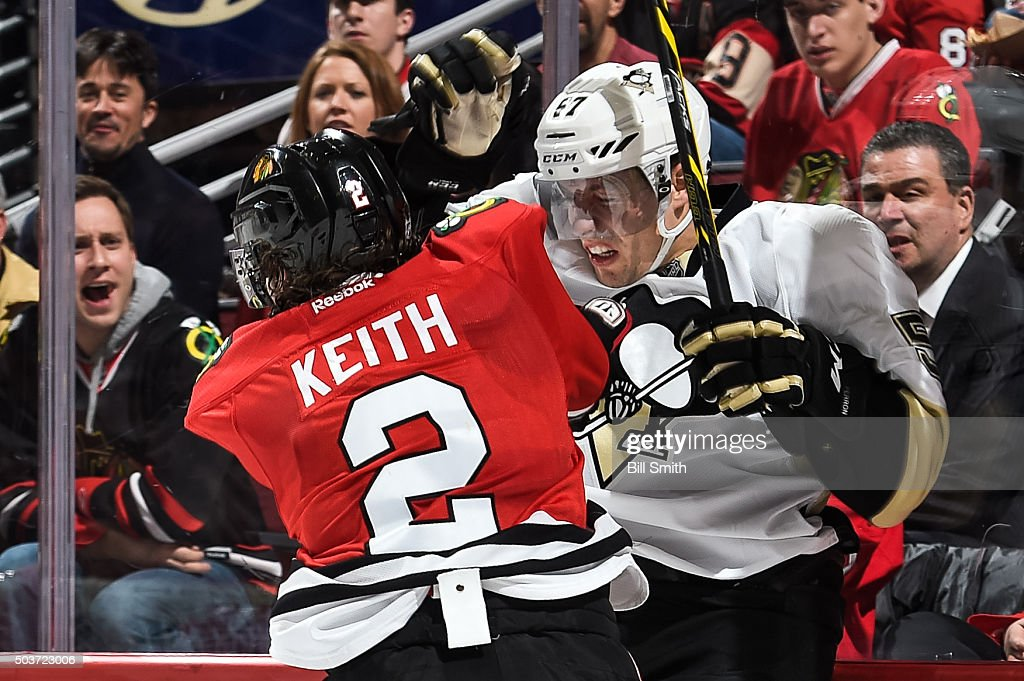 Duncan Keith #2 of the Chicago Blackhawks checks David Perron #57 of the Pittsburgh Penguins into the glass in the second period of the NHL game at the United Center on January 6, 2016 in Chicago, Illinois.