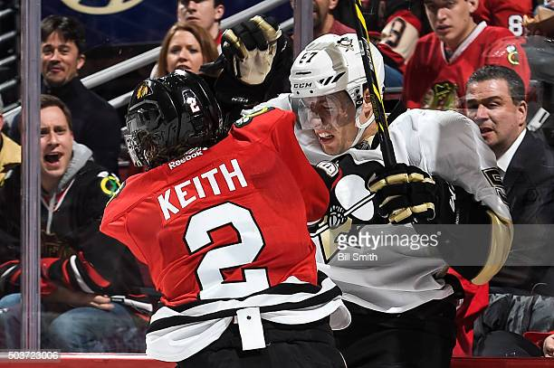 Duncan Keith of the Chicago Blackhawks checks David Perron of the Pittsburgh Penguins into the glass in the second period of the NHL game at the...