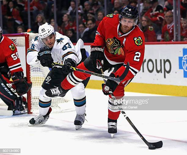Duncan Keith of the Chicago Blackhawks clears the puck under pressure from Matt Nieto of the San Jose Sharks at the United Center on December 20 2015...