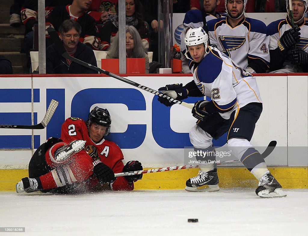 Duncan Keith of the Chicago Blackhawks falls against the boards after battling for the puck with Scott Nichol of the St Louis Blues at the United...