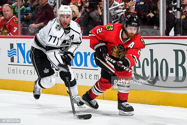 Duncan Keith of the Chicago Blackhawks hits the puck past Jeff Carter of the Los Angeles Kings in the second period at the United Center on October...