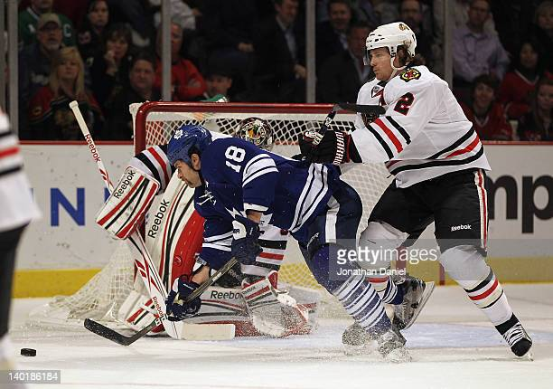 Duncan Keith of the Chicago Blackhawks knocks down Mike Brown of the Toronto Maple Leafs in front of Corey Crawford at the United Center on February...