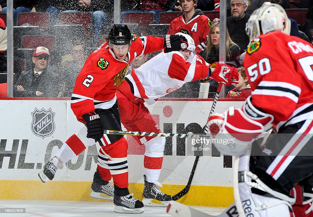 <a gi-track='captionPersonalityLinkClicked' href=/galleries/search?phrase=Duncan+Keith&family=editorial&specificpeople=4194433 ng-click='$event.stopPropagation()'>Duncan Keith</a> #2 of the Chicago Blackhawks slams into <a gi-track='captionPersonalityLinkClicked' href=/galleries/search?phrase=Daniel+Cleary&family=editorial&specificpeople=220490 ng-click='$event.stopPropagation()'>Daniel Cleary</a> #11 of the Detroit Red Wings during the NHL game on January 27, 2013 at the United Center in Chicago, Illinois.