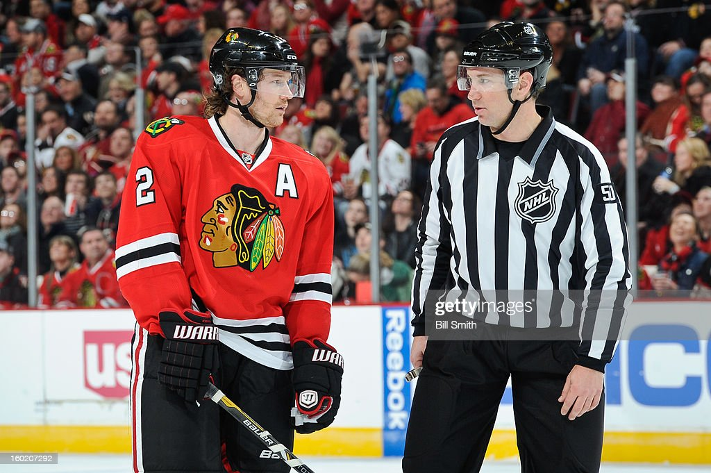 Duncan Keith #2 of the Chicago Blackhawks speaks with linesman Scott Cherrey #50 during the NHL game against the Detroit Red Wings on January 27, 2013 at the United Center in Chicago, Illinois.