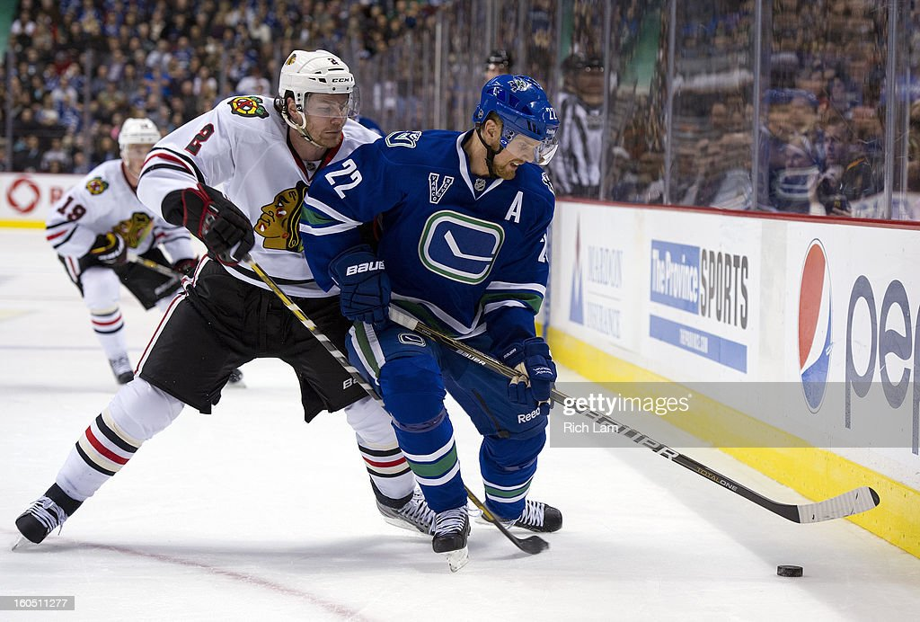 Duncan Keith #2 of the Chicago Blackhawks tries to check Daniel Sedin #22 of the Vancouver Canucks off the puck along the boards during the third period in NHL action on February 01, 2013 at Rogers Arena in Vancouver, British Columbia, Canada.