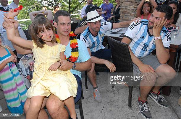 Duncan Pankopf orginally of Munich Germany and his 7yearold daughter Kendall Pankopf celebrate while Argentina fan Omar Ashraf looks on at a World...