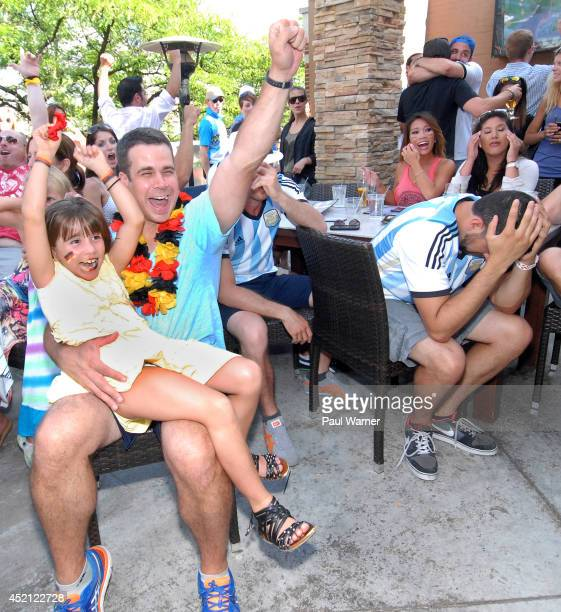 Duncan Pankopf orginally of Munich Germany and his 7yearold daughter Kendall Pankopf celebrate while Argentina fan Omar Ashraf holds his head in his...