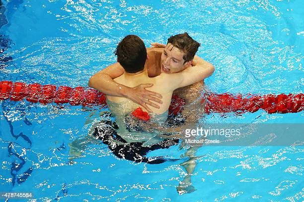 Duncan Scott of Great Britain celebrates winning the gold with teammate and silver medalist Cameron Kurle in the Men's 200m Freestyle final during...
