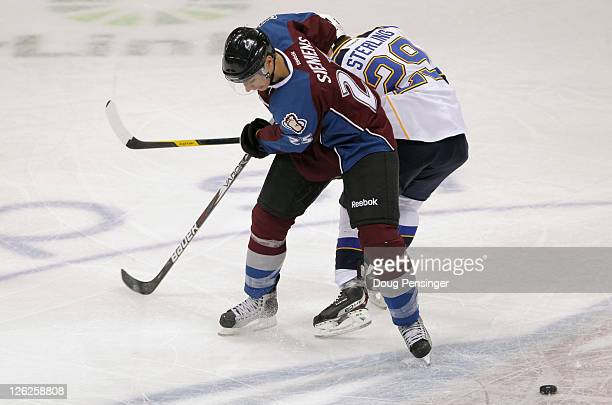 Duncan Siemens of the Colorado Avalanche and Brett Sterling of the St Louis Blues battle for the puck during their preseason game at Pepsi Center on...