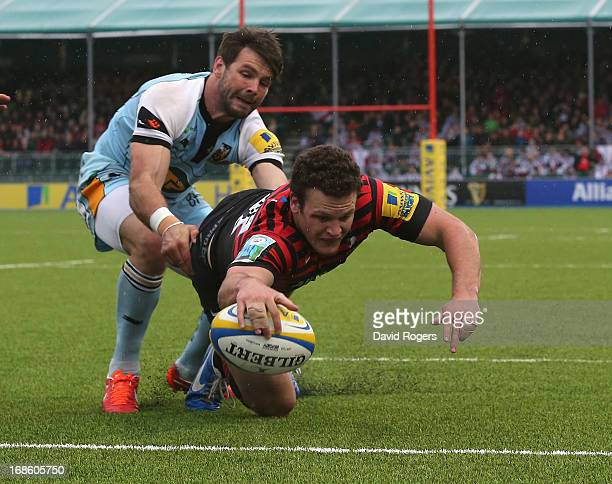 Duncan Taylor of Saracens dives over for a try despite the attention of Ben Foden during the Aviva Premiership semi final match between Saracens and...