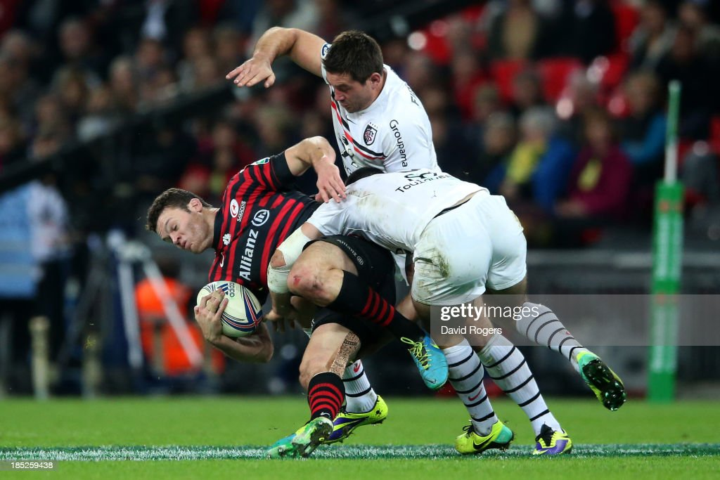 Duncan Taylor of Saracens is tackled by <a gi-track='captionPersonalityLinkClicked' href=/galleries/search?phrase=Jean-Marc+Doussain&family=editorial&specificpeople=7427141 ng-click='$event.stopPropagation()'>Jean-Marc Doussain</a> and <a gi-track='captionPersonalityLinkClicked' href=/galleries/search?phrase=Florian+Fritz&family=editorial&specificpeople=540919 ng-click='$event.stopPropagation()'>Florian Fritz</a> of Toulouse during the Heineken Cup pool three match between Saracens and Toulouse at Wembley Stadium on October 18, 2013 in London, England.