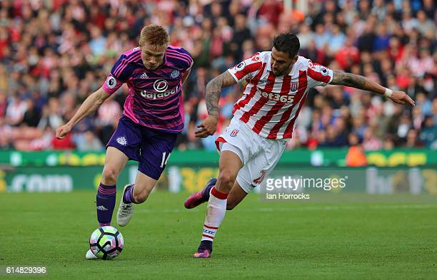 Duncan Watmore of Sunderland tries to beat Geoff Cameron of Stoke City defending during the Premier League match between Stoke City and Sunderland at...