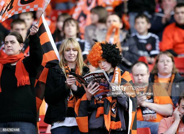 A Dundee United fan reads the match programme