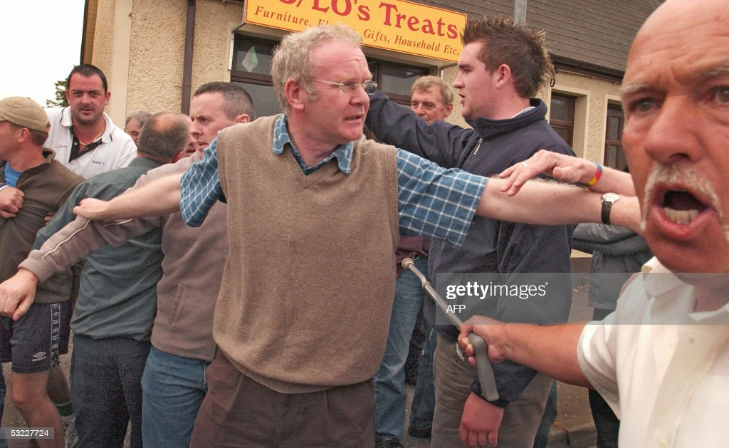 Sinn Fein's Chief Negotiator, Martin McGuinness (C) tries to calm people as the Police remove protesters 12 July 2005 in Dunloy, Northern Ireland. Dunloy residents are protesting the Northern Irelands Parades Commissions decision to let the Protestant Orangemen march though Cathloic areas.The 12th July celebrates the 1690 battle of the Boyne between King William of Orange and Catholic King James. AFP PHOTO/Peter MUHLY