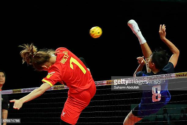 Duong Thi Xuyen of Vietnam attempts to block Sasiwimol Janthasit of Thailand spike during the sepaktakraw women's regu semifinals match at the Expo...