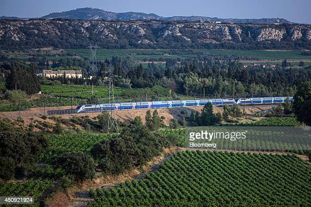A TGV duplex highspeed train operated by Societe Nationale des Chemins de Fer and manufactured by Alstom SA passes through vineyards after departing...