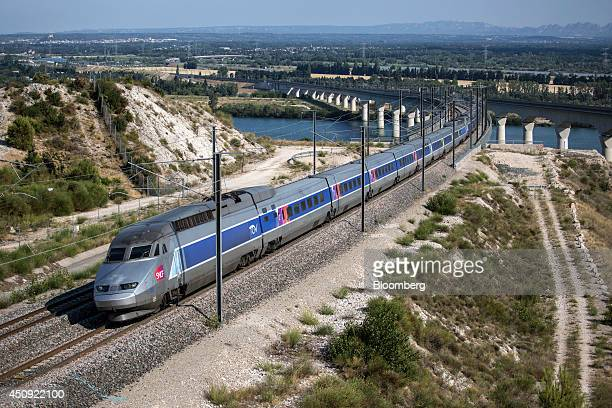 A TGV duplex highspeed train operated by Societe Nationale des Chemins de Fer and manufactured by Alstom SA crosses the River Rhone outside Avignon...
