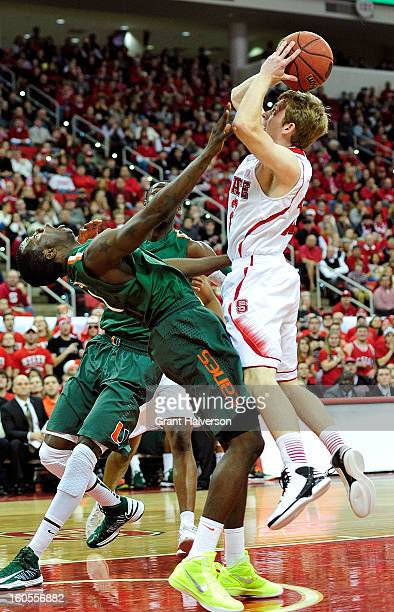 Durand Scott of the Miami Hurricanes is called for a blocking foul as he collides with Tyler Lewis of the North Carolina State Wolfpack during play...