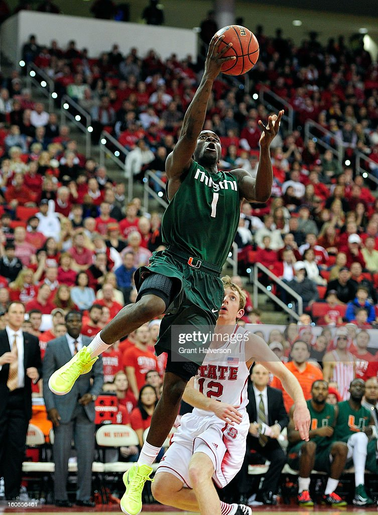 Durand Scott #1of the Miami Hurricanes scores against Tyler Lewis #12 of the North Carolina State Wolfpack during play at PNC Arena on February 2, 2013 in Raleigh, North Carolina. Miami won 79-78.