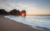 The sunrise through the arch of Durdle Door in Dorset only happens during a brief period in the winter month of December, during the rest of the year the sun's alignment doesn't match the angle of the