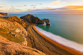 Gorgeous golden light at the famous Durdle Door on the Jurassic Coast, Dorset, UK.