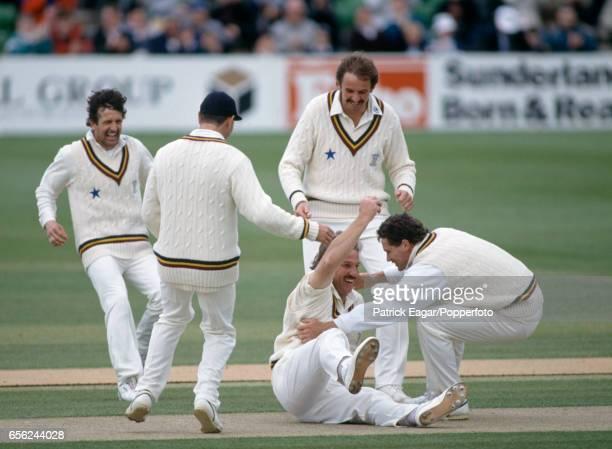 Durham players Paul Parker John Glendenen David Graveney and Dean Jones rush to congratulate Ian Botham after he had taken the wicket of Viv Richards...