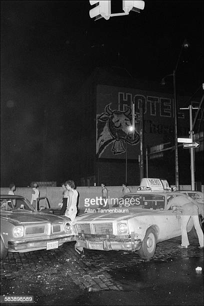 During a blackout pedestrians on onlookers stand around the site of a traffic accident between a car and a taxi New York New York July 13 or 14 1977