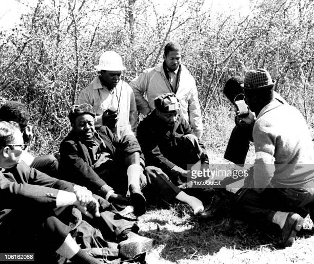 During a break by the side of US Route 80 American Civil Rights leaders Reverend Ralph Abernathy and Dr Martin Luther King Jr and other sit on the...