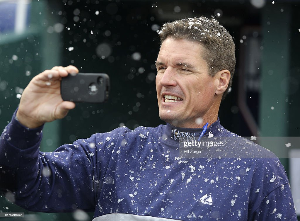 During a delay due to weather, pitching coach Jim Hickey #48 of the Tampa Bay Rays takes a photo of snow falling at Kauffman Stadium on May 2, 2013 in Kansas City, Missouri. The Rays' game against the Kansas City Royals was postponed due to weather.