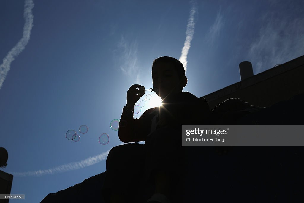 During a lull in militant rocket fire and sillouhetted against fighter jet vapour trails, a young boy plays on the roof of a bomb shelter and blows soap bubbles on November 20, 2012 in Ashkelon, Israel. Hamas militants and Israel are continuing talks aimed at a ceasefire as the death toll in Gaza reaches over 100 with three Israelis also having been killed by rockets fired by Palestinian militants.