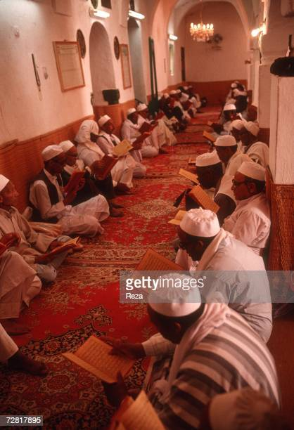 During a mourning men read prayer books during a religious gathering to present condolences to the deceased's family April 2000 in Ghadames Libya