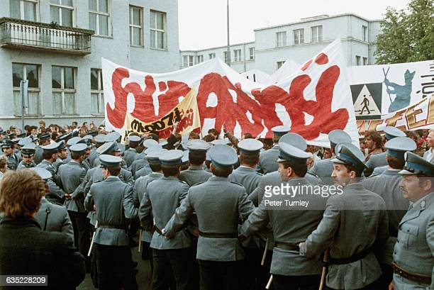 During a visit from Pope John Paul II Polish police officers form a police line to block demonstrators carrying banners reading 'Solidarnosc' the...