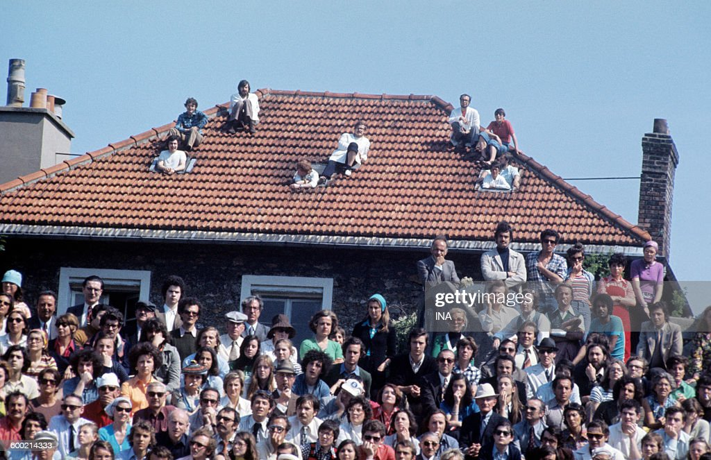 During final of the tennis tournament of Roland Garros, spectators perched on a roof of house situated not far from the center court.