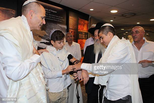 During his Bar Mitzvah ceremony a boy holds out his arm as his older brother helps strap on a set of Tefillin Jerusalem Israel November 5 2015 They...