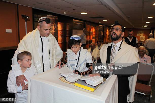 During his Bar Mitzvah ceremony a boy reads from a prayer book Jerusalem Israel November 5 2015 Beside him are from left his younger brother his...