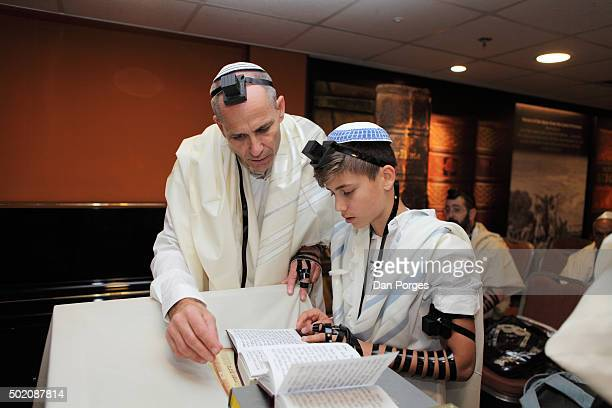 During his Bar Mitzvah ceremony a boy reads from a prayer book Jerusalem Israel November 5 2015 His father stands beside him Both wear Tallit and...