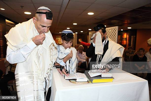 During his Bar Mitzvah ceremony a boy reads from a prayer book Jerusalem Israel November 5 2015 On either side of him are his father and a rabbi All...