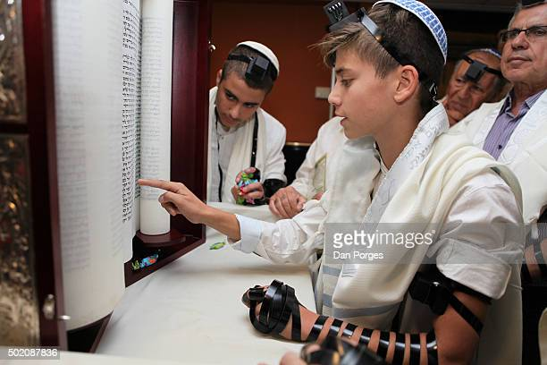 During his Bar Mitzvah ceremony a boy reads from a Torah scroll Jerusalem Israel November 5 2015 He wears a Tallit and a set of Tefillin on his head...