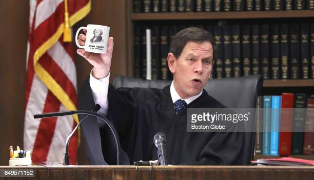 During his long lesson on the courts to the jury Judge Jeffrey Locke holds up the cup given to him by court reporter Nancy King The double murder...