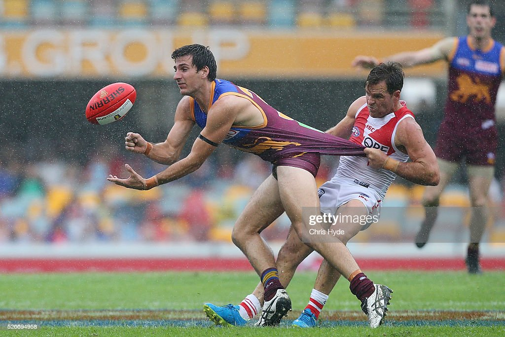 during Sam Mayes of the Lions handballs while tackled by Ben McGlynn of the Swans during the round six AFL match between the Brisbane Lions and the Sydney Swans at The Gabba on May 1, 2016 in Brisbane, Australia.