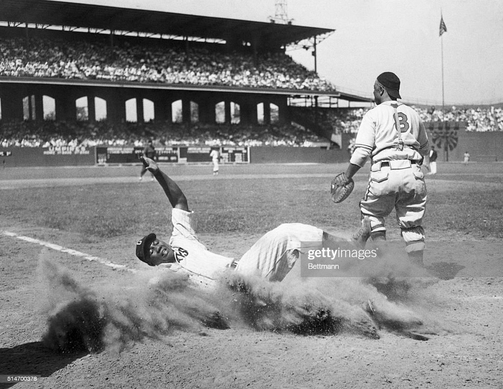 Josh Gibson of the East team creates a cloud of dust as he slides into home after being put out on the play by catcher Ted Radcliffe of the West team...