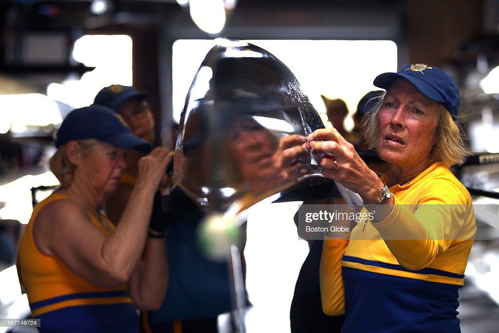 During the annual Head of the Charles Regatta, rowers from the Toowong Rowing Club from Brisbane, Australia carry their boat into the Riverside Boat Club. They finished racing in the senior-master women's eights.