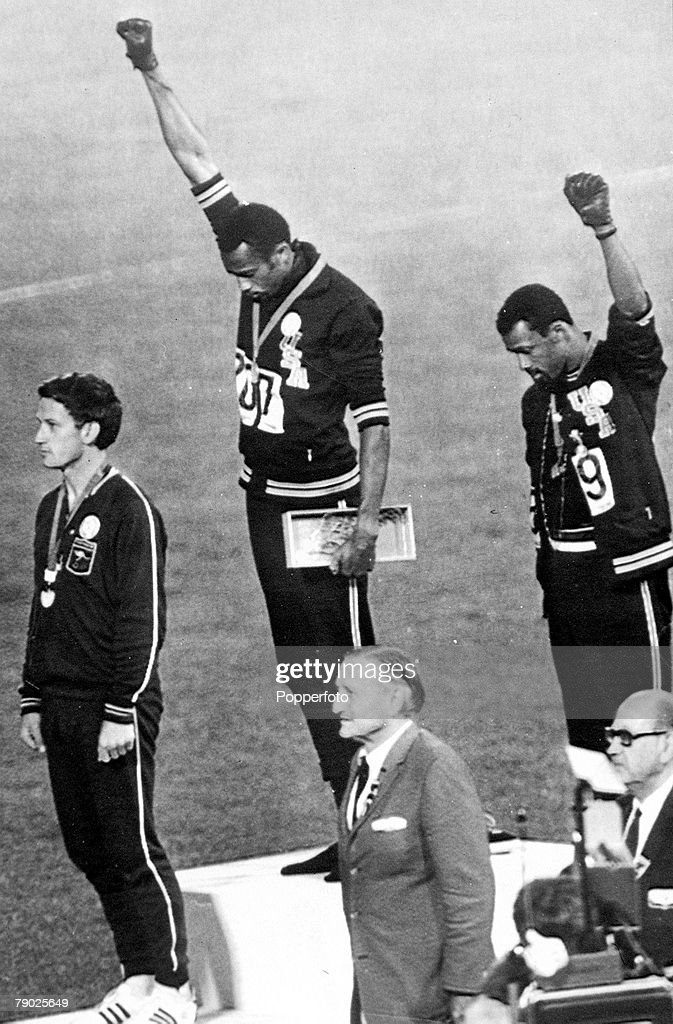 Olympic Games, Mexico City, Mexico, Men's 200 Metres Final, USA gold medalist Tommie Smith (C) and bronze medalist John Carlos give the black power salute as an anti-racial protest as they stand on the podium with Australian silver medallist Peter Norman