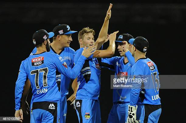 during the Big Bash league match Ben Laughlin of the Strikers celebrates with tem mates the wicket of James Hopes of the Heat between the Brisbane...