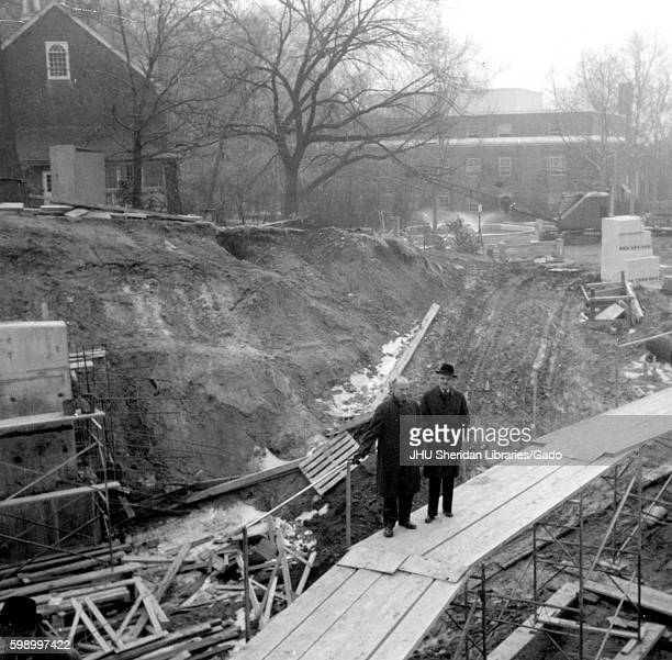 During the early stages of construction of the Milton S Eisenhower Library at Johns Hopkins University two University employees wearing wool coats...