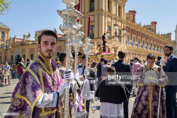 During the Easter week processions with the image of Christ and the virgin Mary parade around Seville Monaguillos priest police and penitents march...